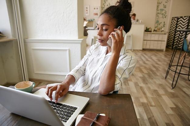 Jonge mooie vrouw freelancer op afstand werken vanuit koffiehuis, bellen met haar smartphone en bericht typen met toetsenbord op laptop Gratis Foto