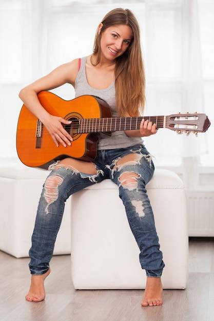Jonge mooie vrouw gitaarspelen Gratis Foto