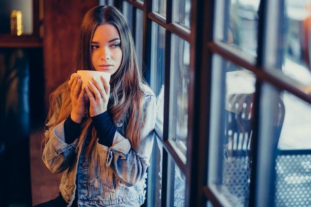 Jonge mooie vrouw het drinken koffie in bar Gratis Foto