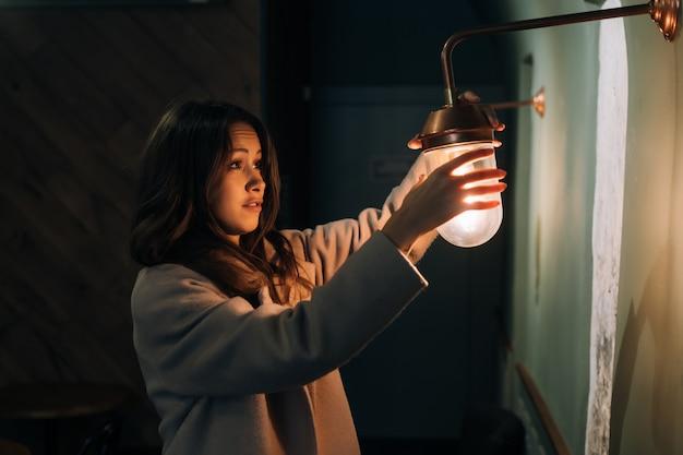 Jonge mooie vrouw houdt in haar hand een kleine wandlamp Gratis Foto