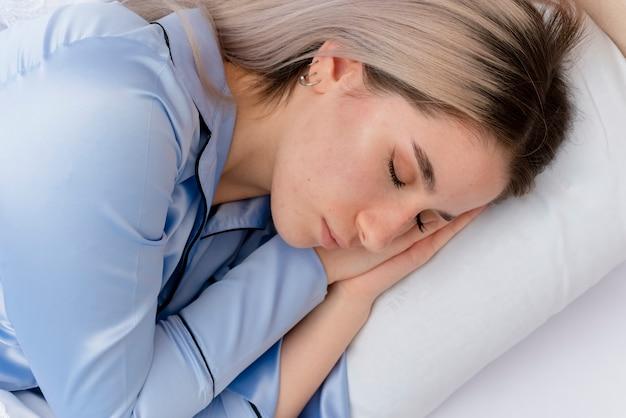 Jonge mooie vrouw in blauwe pyjama's tot op bed Gratis Foto