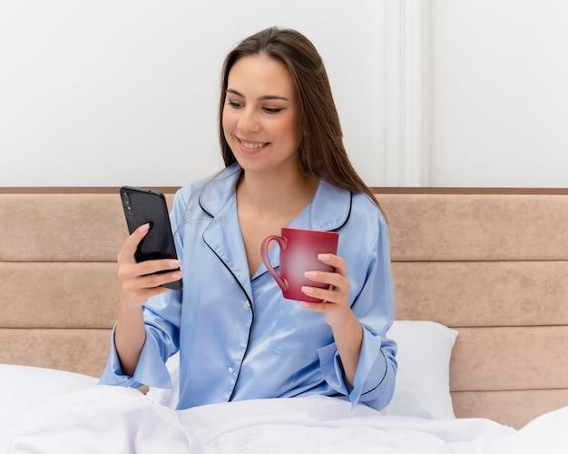 Jonge mooie vrouw in blauwe pyjama zittend op bed met kopje koffie met smartphone kijken met glimlach op gezicht in slaapkamer interieur op lichte achtergrond Gratis Foto