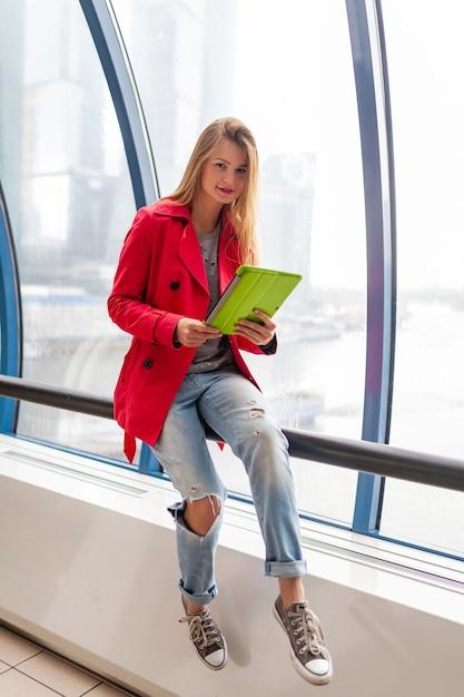 Jonge mooie vrouw in casual de tabletlaptop van de uitrustingsholding in stedelijk gebouw Gratis Foto