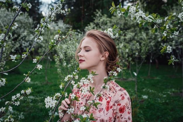 Jonge mooie vrouw in de kers-bloeiende tuin. Premium Foto