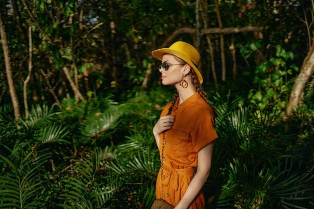 Jonge mooie vrouw in de wildernis van tropen met hoedengangen in het park, naturalist Premium Foto