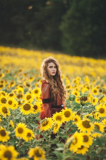 Jonge mooie vrouw in een jurk onder bloeiende zonnebloemen. agro-cultuur. Premium Foto
