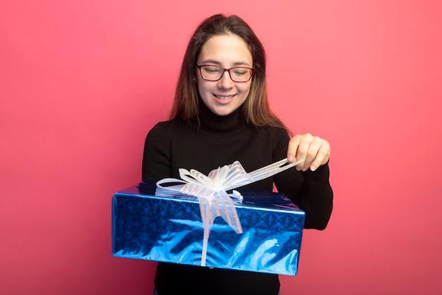 Jonge mooie vrouw in een zwarte coltrui en glazen die geschenkdoos houden die ernaar kijken met een blij gezicht dat zich over roze muur bevindt Gratis Foto