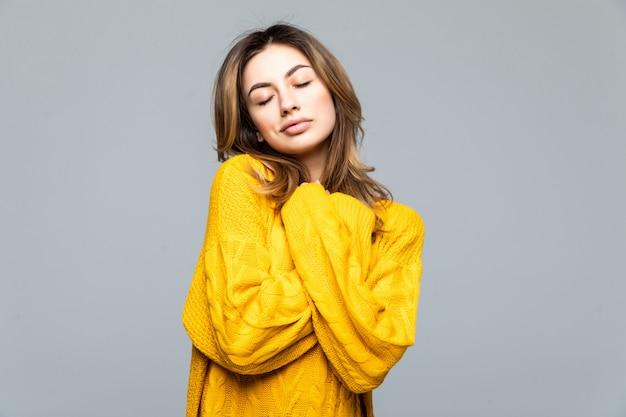 Jonge mooie vrouw in gele toevallige sweater die zich met gekruiste wapens bevinden die op grijze muur worden geïsoleerd Gratis Foto