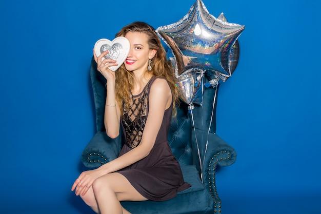 Jonge mooie vrouw in grijze jurk zittend op een blauwe fauteuil met zilveren hart Gratis Foto
