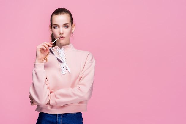 Jonge mooie vrouw in roze geïsoleerde sweater en zonnebril Premium Foto