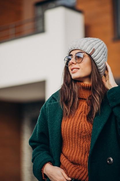Jonge mooie vrouw in warme jas bij het huis Gratis Foto