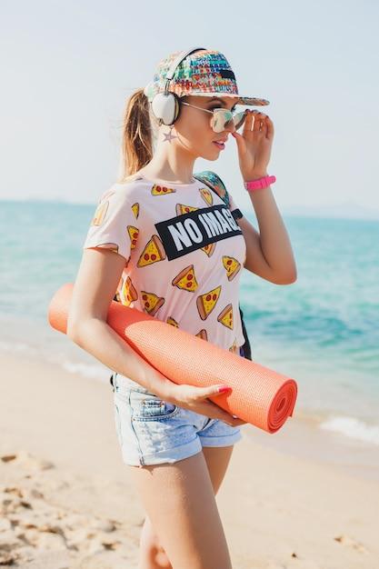 Jonge mooie vrouw lopen op het strand met yogamat, luisteren naar muziek op koptelefoon, hipster sport swag stijl, denim shorts, t-shirt, rugzak, pet, zonnebril, zonnig, zomerweekend, vrolijk Gratis Foto