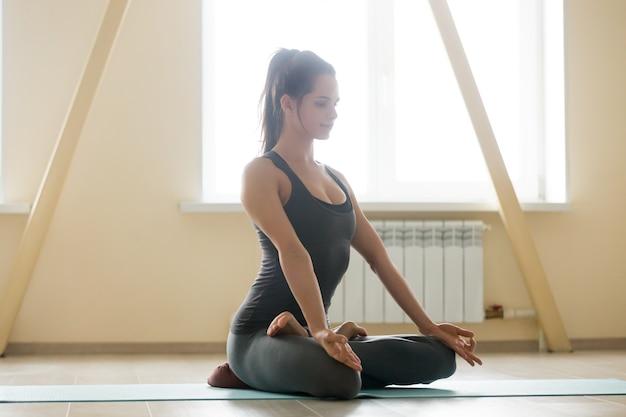 Jonge mooie vrouw mediteren thuis Gratis Foto