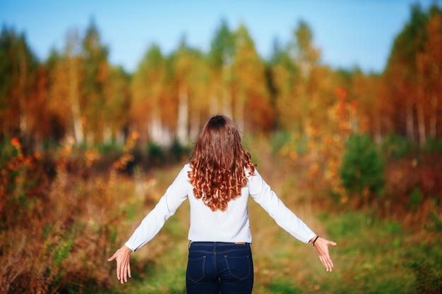 Jonge mooie vrouw. meisje met lang haar, van rug. herfst Premium Foto