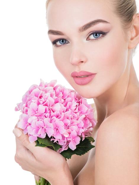 Jonge mooie vrouw met bloemen dichtbij gezicht. Gratis Foto