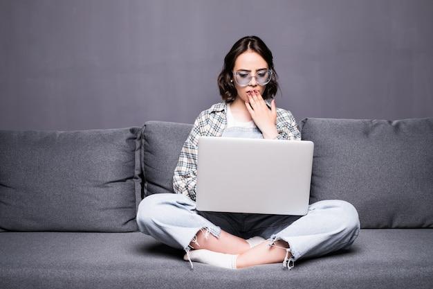 Jonge mooie vrouw met bril met behulp van een laptopcomputer thuis zittend op de bank Gratis Foto