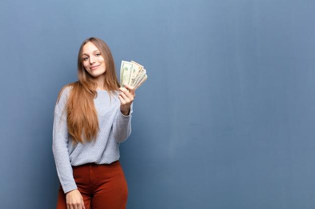 Jonge mooie vrouw met dollarbankbiljetten tegen blauwe muur met een exemplaarruimte Premium Foto
