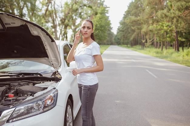 Jonge mooie vrouw met een kapotte auto op de weg Premium Foto