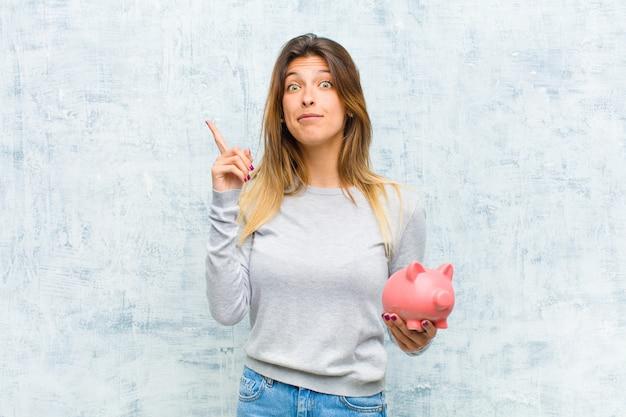 Jonge mooie vrouw met een spaarvarken tegen grungemuur Premium Foto