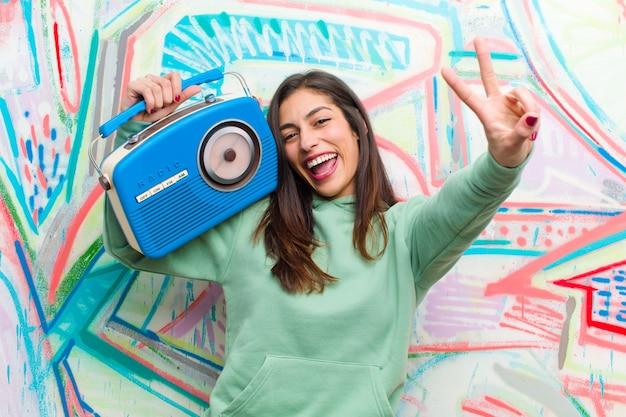 Jonge mooie vrouw met een vintage radio tegen graffitimuur Premium Foto