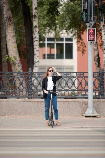 Jonge mooie vrouw met elektrische scooter staan bij verkeerslichten en wachten op het groene licht om de weg over te steken terwijl ze zich haasten naar het werk Premium Foto