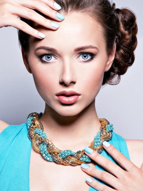 Jonge mooie vrouw met juwelen. meisjesmanier in blauwe kleding die bijouterie draagt. aantrekkelijk model met blauwe nagels. Gratis Foto