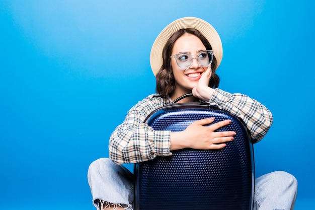 Jonge mooie vrouw met koffer met zonnebril en strooien hoed klaar voor zomervakantie Gratis Foto