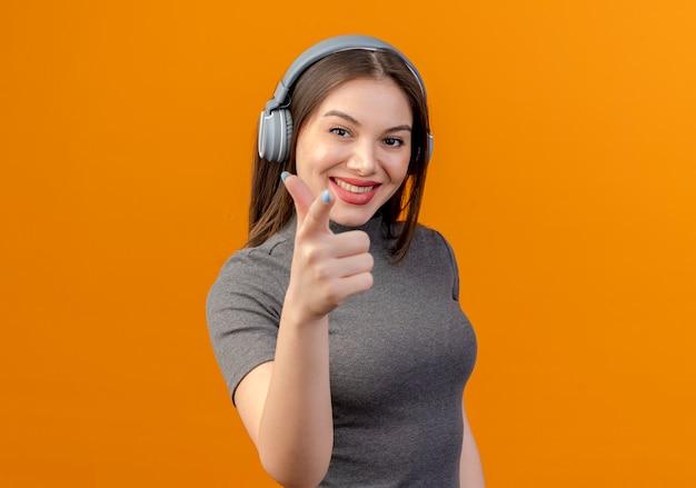 Jonge mooie vrouw met koptelefoon luisteren naar muziek geïsoleerd op oranje Gratis Foto