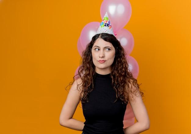 Jonge mooie vrouw met krullend haar die bos van luchtballons houden die opzij kijken met sceptisch expressin concept van de verjaardagsfeestje die zich over oranje muur bevinden Gratis Foto