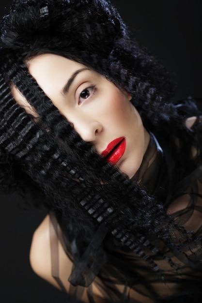 Jonge mooie vrouw met krullend haar en rode lippen Premium Foto