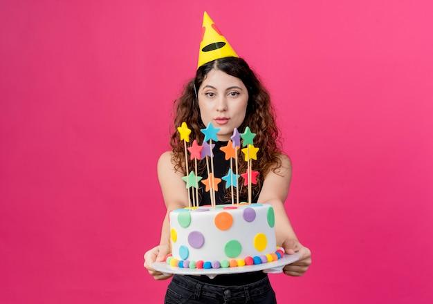 Jonge mooie vrouw met krullend haar in een vakantie glb bedrijf verjaardagstaart gelukkig en positief verjaardagsfeestje concept staande over roze muur Gratis Foto