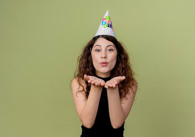 Jonge mooie vrouw met krullend haar in een vakantie glb blaast een kus met de handen voor haar verjaardagsfeestje concept staande over lichte muur Gratis Foto