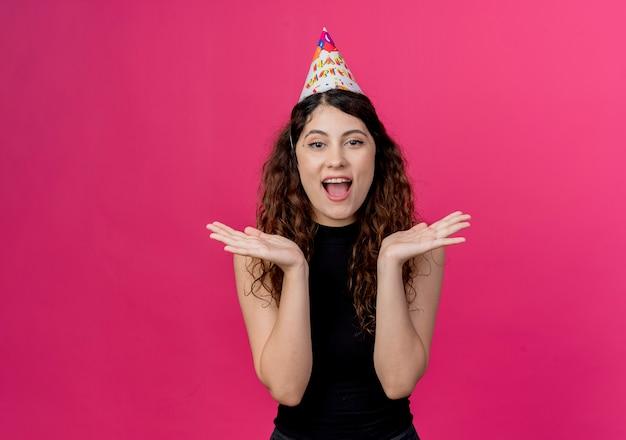 Jonge mooie vrouw met krullend haar in een vakantie glb verrast en gelukkig verjaardagsfeestje concept staande over roze muur Gratis Foto