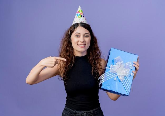 Jonge mooie vrouw met krullend haar in een vakantie pet met de doos van de verjaardagscadeau wijzend met de vinger naar het glimlachend vrolijk verjaardagsfeestje concept staande over blauwe muur Gratis Foto