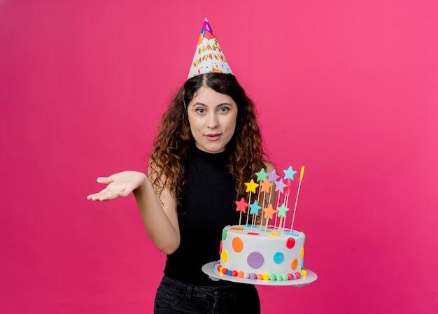 Jonge mooie vrouw met krullend haar in een vakantiepet met verjaardagstaart lachend met arm uit als vragend verjaardagsfeestje concept staande over roze muur Gratis Foto