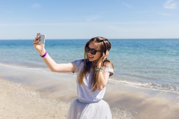Jonge mooie vrouw met lang haar staat in de buurt van blauwe zee Gratis Foto