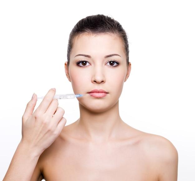 Jonge mooie vrouw met medische spuit in de buurt van de lippen Gratis Foto