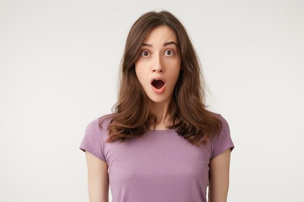 Jonge mooie vrouw met prachtig haar ziet er geschokt, stomverbaasd, opengesperde kaak uit Gratis Foto