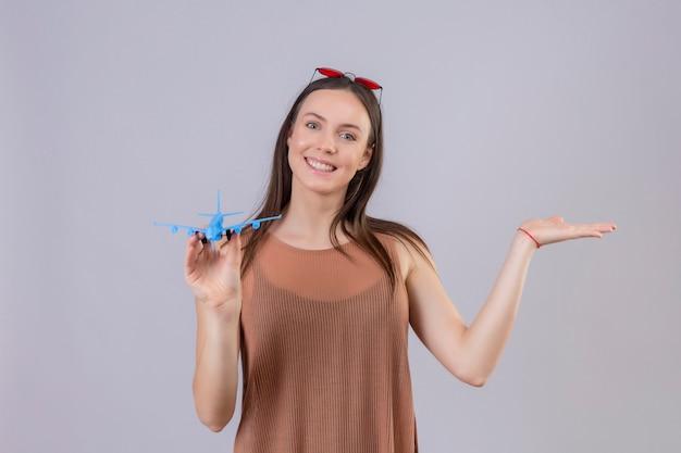 Jonge mooie vrouw met rode zonnebril op hoofd bedrijf speelgoed vliegtuig presenteren met arm van de hand lachend met blij gezicht staande op witte achtergrond Gratis Foto