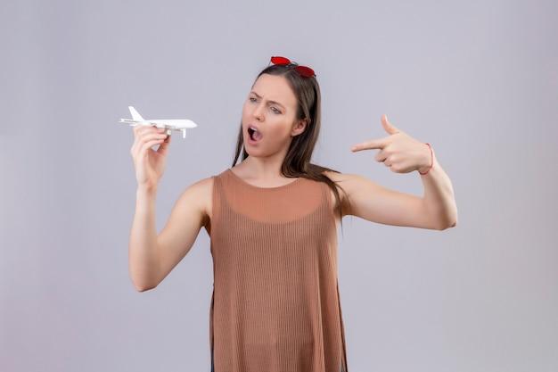 Jonge mooie vrouw met rode zonnebril op hoofd bedrijf speelgoed vliegtuig wijzend met de vinger naar het verrast en verbaasd staande op witte achtergrond Gratis Foto
