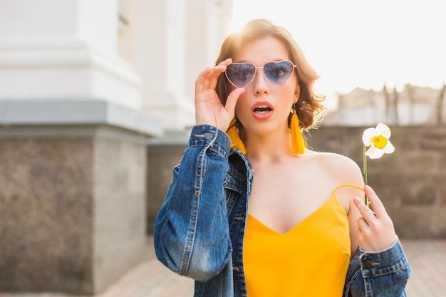 Jonge mooie vrouw met verbaasde gezichtsuitdrukking, emotionele, geschokte emotie, stijlvolle kleding dragen, spijkerjasje, gele top, bloem vasthouden, zonnige zomer, trendy grappige blauwe zonnebril Gratis Foto