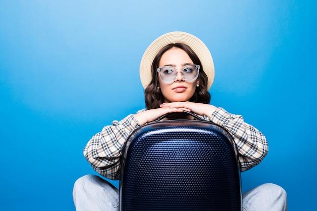 Jonge mooie vrouw met zonnebril en strohoed met het paspoort van de kofferholding vóór vlucht wachtend vliegtuig Gratis Foto
