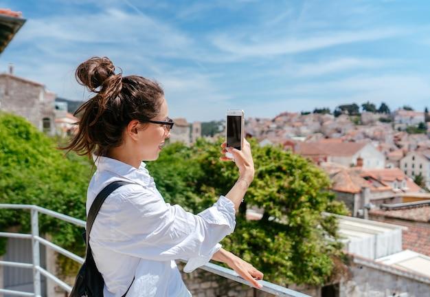 Jonge mooie vrouw op een balkon met uitzicht op een kleine stad in kroatië Gratis Foto