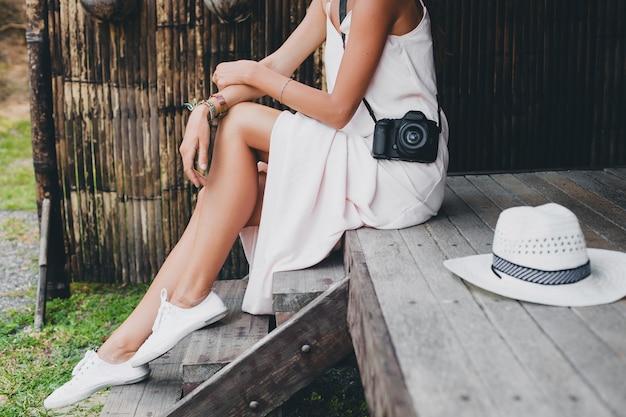 Jonge mooie vrouw op tropische vakantie in azië, zomerstijl, witte boho-jurk, sportschoenen, digitale fotocamera, reiziger, strooien hoed, benen close-up details Gratis Foto