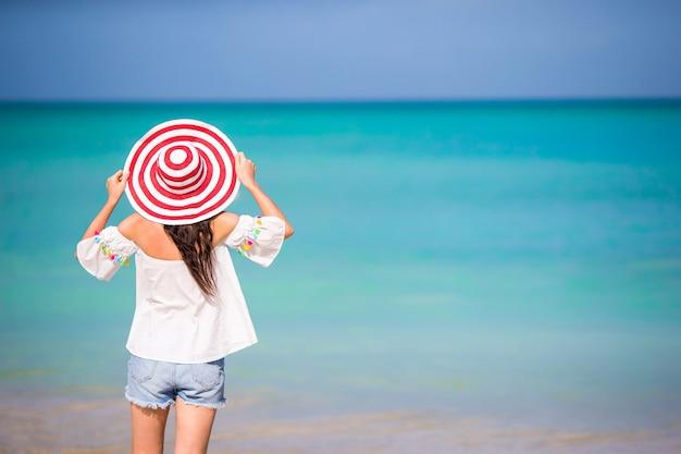 Jonge mooie vrouw op wit zand tropisch strand. achtermening van kaukasisch meisje Premium Foto