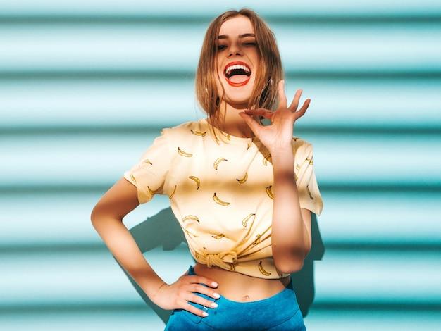 Jonge mooie vrouw op zoek. trendy meisje in casual zomer gele t-shirt kleding. het grappige model stellen dichtbij blauwe muur. ok teken met hand en vingers tonen. Gratis Foto