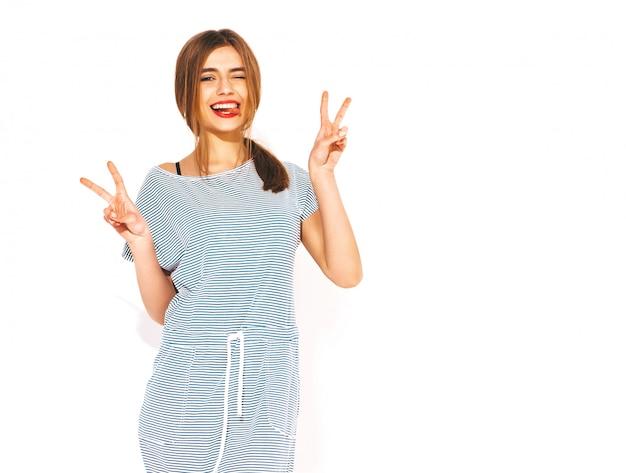 Jonge mooie vrouw op zoek. trendy meisje in casual zomer gestreepte jurk. positief grappig model. tong en vredesteken tonen Gratis Foto