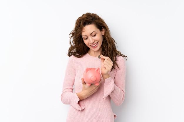 Jonge mooie vrouw over geïsoleerde holding een grote spaarpot Premium Foto