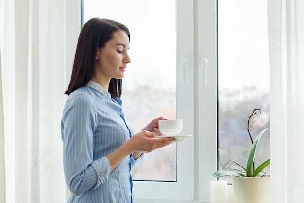 Jonge mooie vrouw permanent thuis in de buurt van venster met kopje koffie, winterseizoen ruimte, lichte gordijnen, kopie ruimte Premium Foto