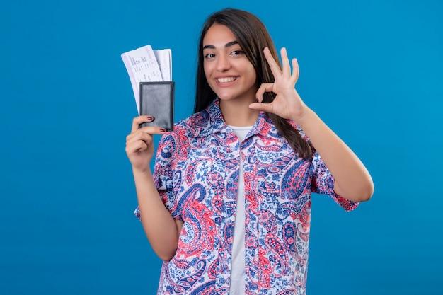 Jonge mooie vrouw toeristische bedrijf paspoort met kaartjes kijken camera glimlachend vrolijk doen ok teken staande over geïsoleerde blauwe achtergrond Gratis Foto